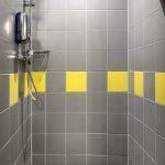 Standard huoneen suihkussa on keltaharmaa laatoitus