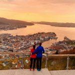 Pariskunta katsomassa Bergenin kaupunkia auringonlaskun aikaan Floyen vuorelta