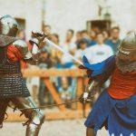 Keskiaikaisiin ritariasuihin pukeutuneet hahmot miekkataisteluesityksessä.