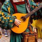 Keskiaikaiseksi trubaduuriksi pukeutunut henkilö esiintymässä.