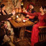 Keskiaikaisiin asuihin pukeutunut seurue kohottaa maljoja puisen ruokapöydän äärellä.
