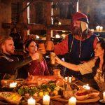 Keskiaikaisiin asuihin pukeutunut seurue kohottaa maljoja illallisella.