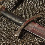 Lähikuva keskiaikaisesta miekasta ja ketjupanssarista.