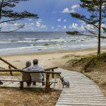 PAriskunta istuu penkillä merelle katsellen