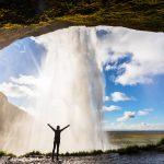 Henkilö seisoo Seljalandsfossin vesiputouksen takana ja levittää kädet ilmaan.
