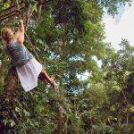 Jurmala Tarzans -huvipuisto Tyttö kiipeilee liaanilla.