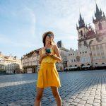 Keltaiseen mekkoon pukeutunut nainen hymyilee Prahan vanhankaupungin aukiolla puhelin kädessään.