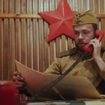 Neuvostoliiton sotilasasuun pukeutunut mies pitää punaista puhelinta korvallaan ja katsoo kansiota.