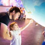 Pieni lapsi osoittaa tiedenäyttelyssä isälleen mielenkiintoista kohdetta.