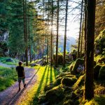 Vaeltaja kulkee Kossdalssvegenin vaellusreittiä auringon paistaessa matalalta.