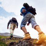 Kaksi vaeltajaa nousee mäkeä kallioisessa maastossa.