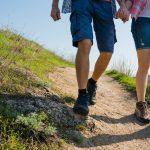 Pariskunta kävelee polkua alas käsi kädessä.