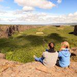 Kaksi retkeilijää istuu kallion reunalla ja katselee Asbyrgin kanjonia.