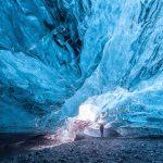 Henkilö seisoo suuren jääluolan sisällä.