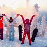Lumilautailijat heittävät lunta ilmaan tunturimaisemissa.