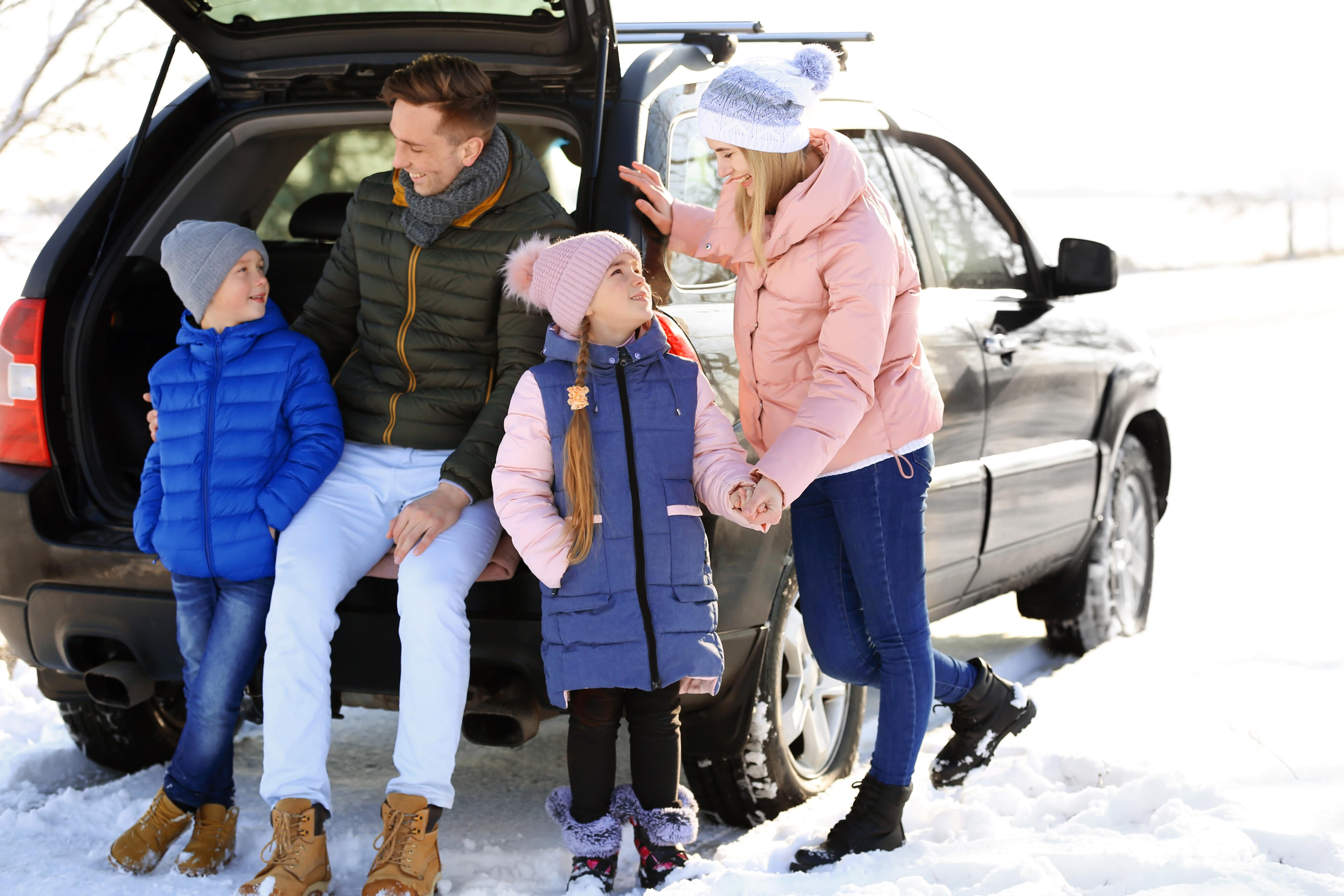Iloinen perhe pitämässä taukoa auton edessä talvipäivänä.