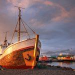 Kalastaja-alus maihin vedettynä venesatamassa auringonlaskun kajossa.