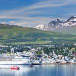 Akureyrin kaupunki mereltä kuvattuna, risteilyaluksia sekä pienempi laiva kaupungin edustalla.