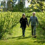 Pariskunta käsikkäin puutarhassa kävelyllä