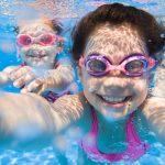 Tyttö ottaa pikkusiskon kanssa selfien veden alla.