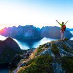 Vuoren päälle kiivennyt nainen nostaa kädet ilmaan keskiyön auringon paistaessa.