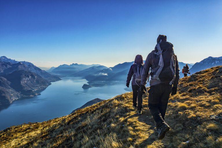 Seurue vaeltamassa vuori- ja merimaisemissa kirkkaana päivänä.