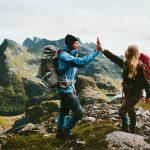 Vuorelle vaeltaneet mies ja nainen lyövät kädet yhteen onnistumisen merkiksi.