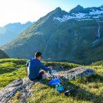 Mies pitää taukoa aurinkoisena päivänä Alppimaisemissa ja valmistaa eväitä.