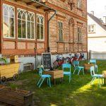 Tuoleja ja pöytiä vanhan talon edustalla