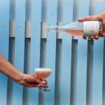 Käsi kaataa viiniä lasiin, taustalla sininen seinä