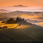 Aurinko nousee Toscanan kumpuilevalla maaseudulla.