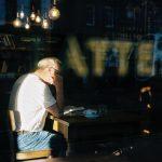 Mies lukee lehteä baarissa ikkunan takana