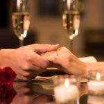 PAriskunnan kädet pöydällä, taustalla kuohuviiniä