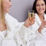 Kylpylätakkeihin pukeutuneet ystävykset kohottavat kuohuviinilaseja.