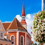 Kirkko ja rakennuksia kesäisenä päivänä, edustalla kukka-amppeli.