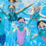 Ryhmä lapsia ilmeilee kameralle veden alla.