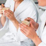 Kaksi naista nauttii lämmintä sitruunavettä kylpytakit päällään.