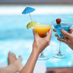 Pariskunta kohottaa värikkäitä drinkkejä altaan reunalla.