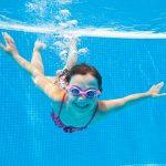 Tyttö sukeltaa ja hymyilee kameralle veden alla.
