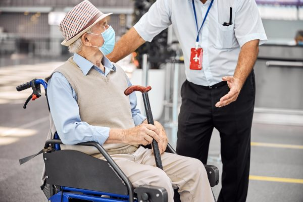 Henkilökuntaan kuuluva mies avustaa pyörätuolissa istuvaa maskilla suojautunutta iäkästä matkailijaa lentoasemalla.