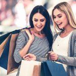 Kaksi naista ihastelee ostoskassien sisältöä.
