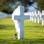 Valkoisia ristejä hautausmaalla, lähimmän ristin vieressä pieni Yhdysvaltojen lippu.