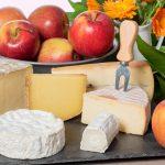 Normandialaisia juustoja ja omenoita tarjottimella.