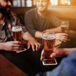 Kaveriporukka istuu iloisena pubissa oluttuopit kädessä.