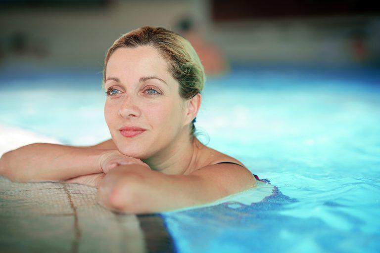Nainen nojaa altaan reunaan kylpylässä.