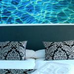 Kaksi tyynyä sängyllä ja vesiaiheinen taulu taustalla