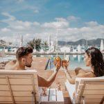 Pariskunta kilistää drinkkejä altaalla