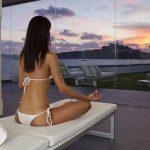 Nainen meditoi iltamaiseman äärellä