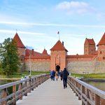 Ihmisiä kulkee puista siltaa pitkin kohti linnaa.
