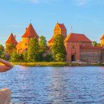 Hattupäinen tyttö istuu rannalla Trakain linnan edustalla ilta-auringossa.